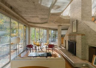 The living spaces and dining room are connected and feature an original fireplace. The concrete foundation is exposed throughout, accentuating the house's angular lines.