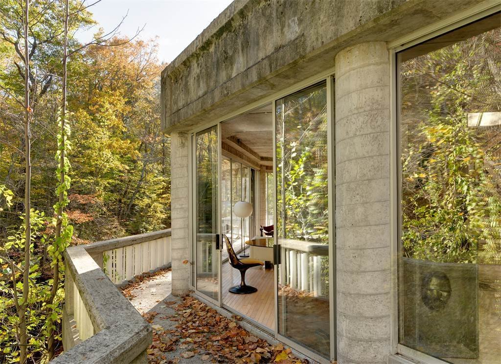 You can walk along the thin balcony that lines the edge of the house, where you'll enjoy incredible views of the river.  Photo 10 of 11 in The One-of-a-Kind Home of the Late Architect John Black Lee Drops to $750K