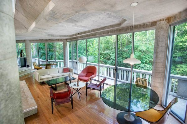 The interior hosts an open floor plan and looks out over a balcony that runs the length of the structure along the river side.  Photo 8 of 11 in The One-of-a-Kind Home of the Late Architect John Black Lee Drops to $750K
