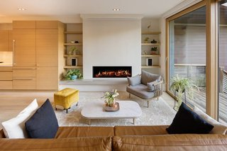 Thanks to a hidden screen that rolls down over the fireplace, the living room doubles as a TV or movie room.