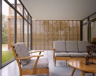 Shown here is the screened porch that looks out through glass on one side and screened red cedar slabs on the other.