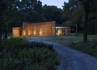 The Coffou Cottage sits in an L-shaped configuration at the end of a private road.  This image shows how red cedar is utilized to create thin slats along the facade, as well as horizontal and vertical board-and-batten siding.
