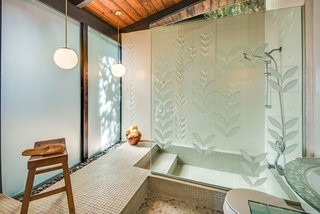 "The master bathroom has been updated with George Nelson's sculptured tiles from Pomona Tile Manufacturing Co. The shower wall features the ""Laurel Leaf"" pattern, which is a bas-relief treatment of a single diagonal leaf motif with both raised and recessed areas. The most recent homeowner also installed etched glass to mimic the motif of the tile."