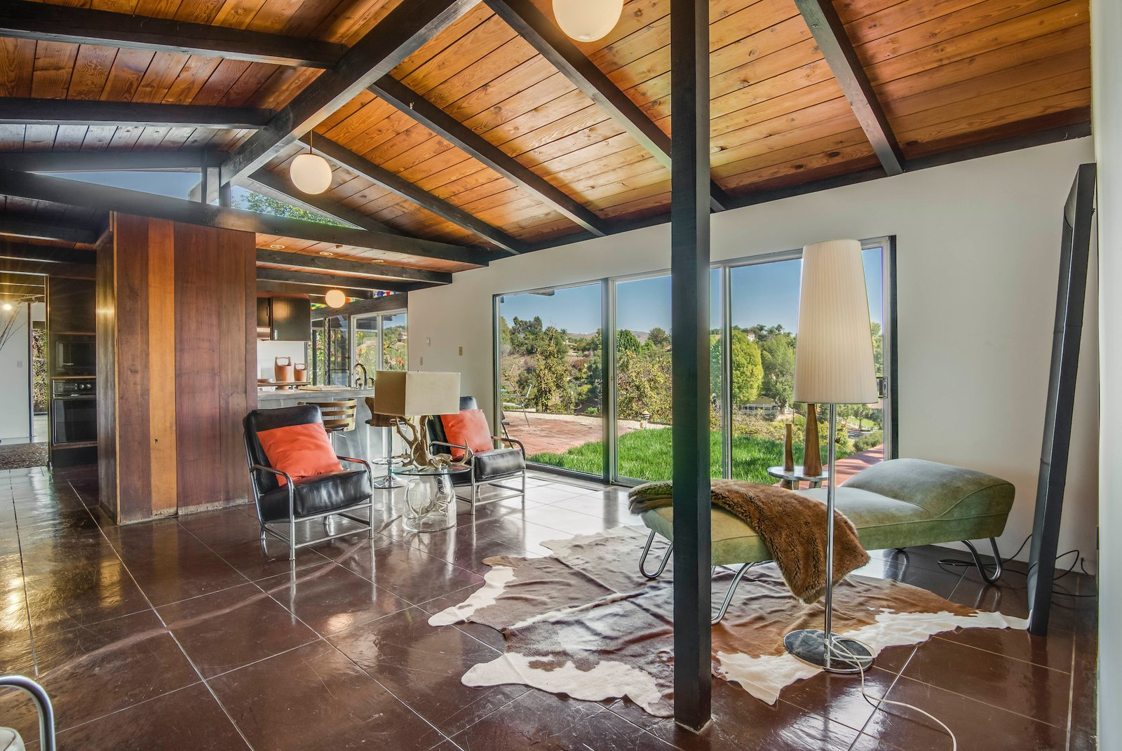 The interior features lossy finished concrete floors and some original globe lights overhead.  Photo 7 of 10 in This Midcentury Home For Sale Is Not Your Regular Ranch House