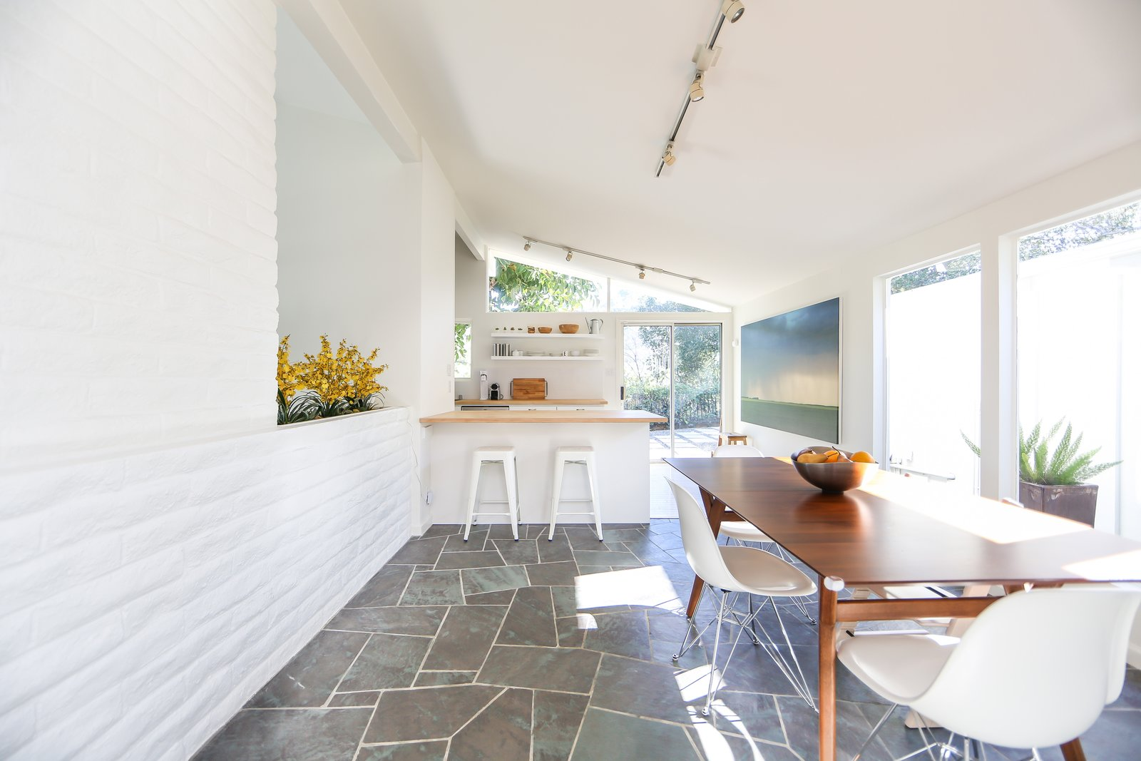 Though the main bones have been kept intact, one of the past owners installed slate flooring in the entryway, hallway, and dining area (shown here), which leads into the lengthy kitchen.  Photo 4 of 10 in If You Crave Bright, Light-Filled Spaces, This Midcentury Home For Sale Could Be the One
