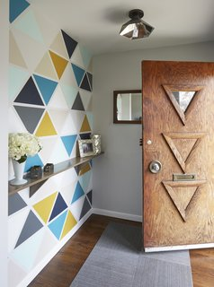 Carly and Brad rearranged the former entry closet area to create a small vestibule that would block the direct view to the kitchen upon arrival. Instead of covering it with wallpaper, they created a custom stencil and painted it themselves on Christmas Eve. They used the colors that can be found throughout the house, while the triangles take cues from the carvings on the original door.