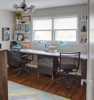 Carly uses one of the bedrooms upstairs as her office, which is furnished with movable Ikea desk tops that fit the extent of the wall.