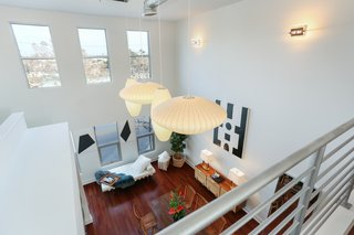 Shown here is the view of the living space from the lofted bedroom. The loft is being sold with a four-piece set of George Nelson bubble lamps that hang from the twenty-foot ceiling.