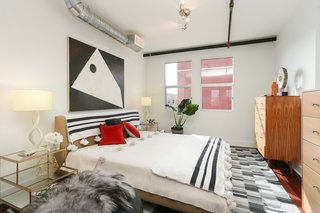 The bedroom is tucked into the loft space and sits under exposed air ducts and pipes—both of which add to the industrial vibe.