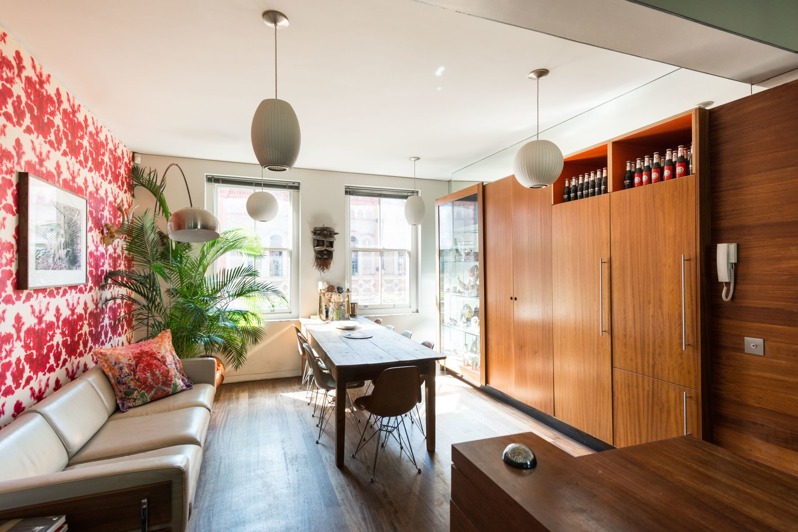 The dining space and kitchen are connected in a long, narrow section, and offer floor-to-ceiling cupboards.  Photo 4 of 11 in Formerly Home to an Artist and Knitwear Designer, a Commercial Space-Turned-Dwelling Hits the Market