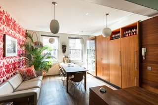 The dining space and kitchen are connected in a long, narrow space that's lined with floor-to-ceiling cabinets.