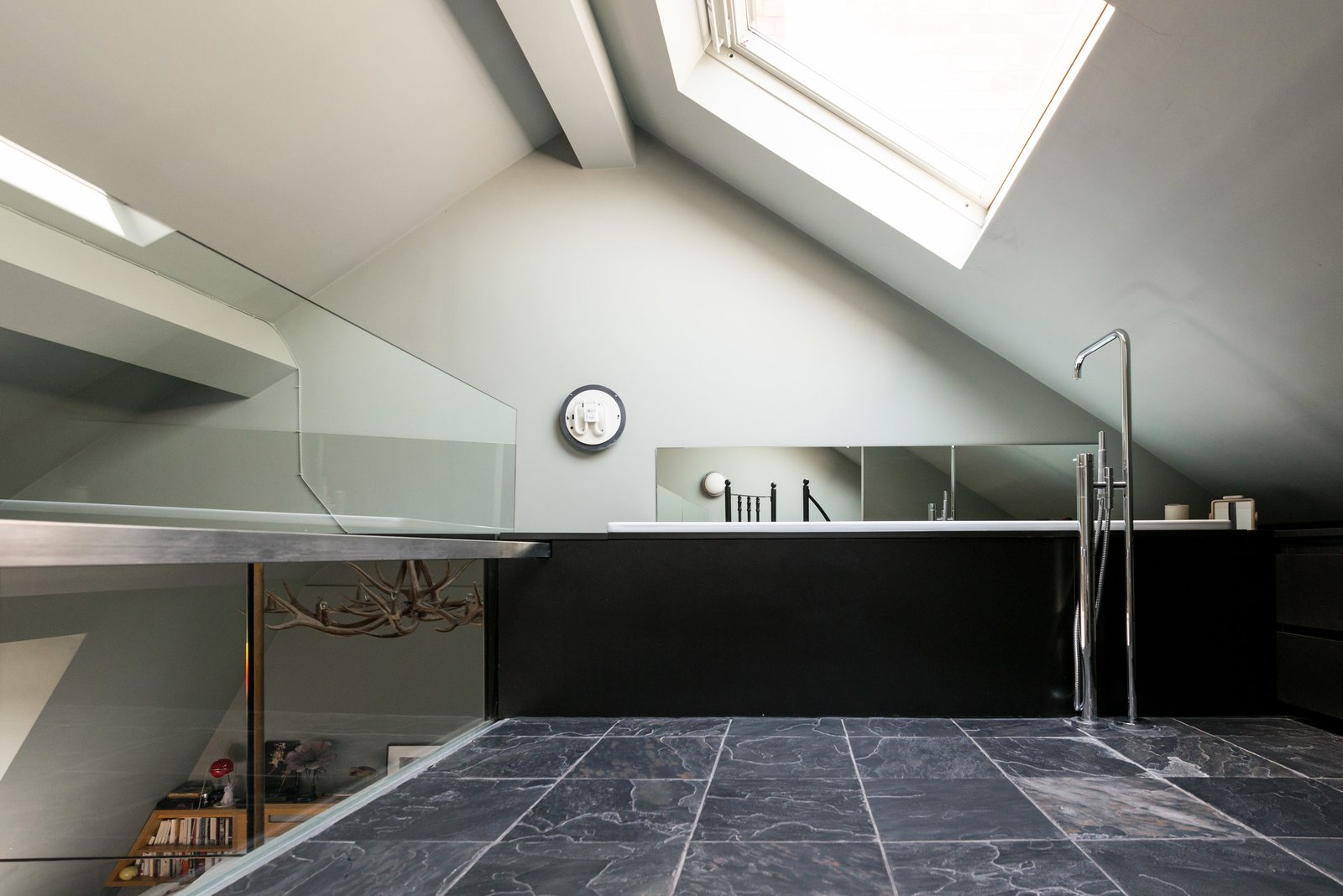 When you climb the spiral stairs, you're led to the en-suite bathroom on the mezzanine level, which revels in natural light, thanks to a substantial angled skylight.  Photo 8 of 11 in Formerly Home to an Artist and Knitwear Designer, a Commercial Space-Turned-Dwelling Hits the Market