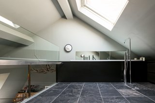 When you climb the spiral stairs, you're led to the en-suite bathroom on the mezzanine level, which revels in natural light—thanks to a substantial angled skylight above,