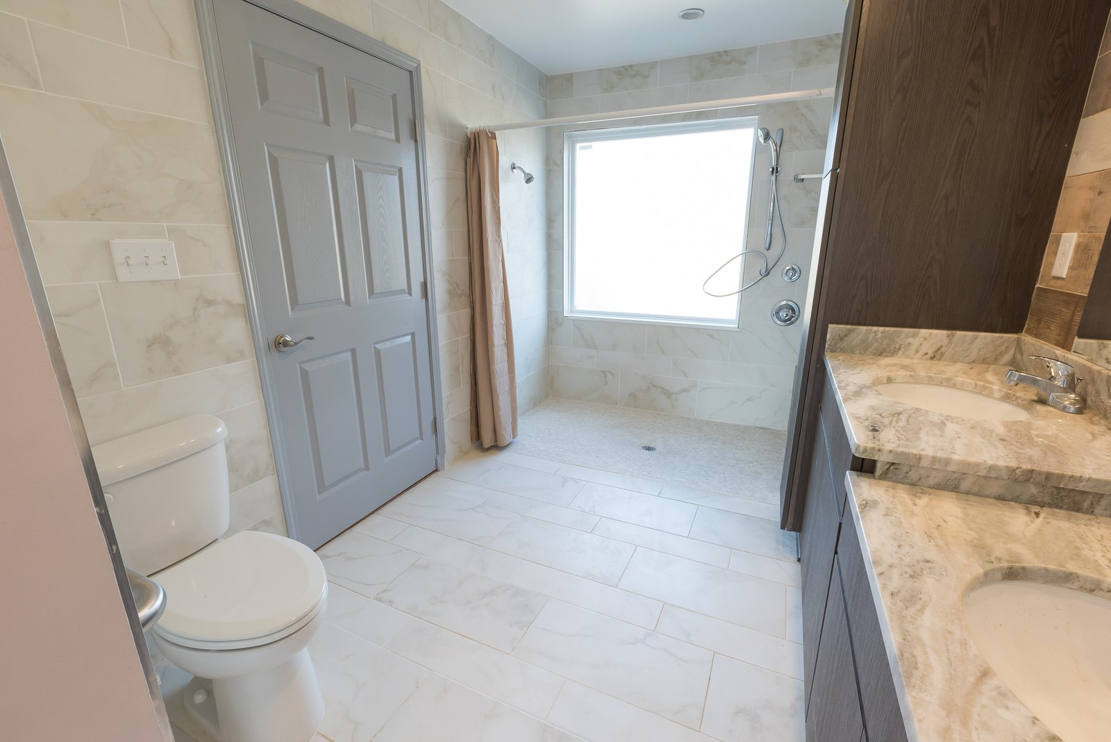 The final result includes an accessible layout with plenty of storage space and dual sinks at different levels for both the adults and the young ones.  Photo 9 of 9 in The Winning Vision From a Universal Design Competition Is Brought to Life For a Veteran