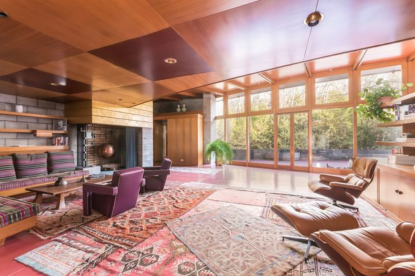 """The original living room holds a number of furniture pieces that Wright designed. Since he enjoyed interweaving textures and materials, he created a fireplace that's made of concrete block—but painted with gold leaf. Gricar explains, """"He loved the material play between fancy and utilitarian."""""""