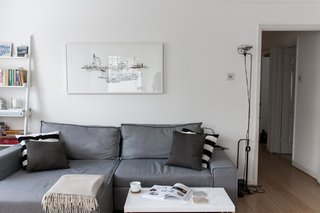 For the small yet open living space, Silvia brought in a sofa bed from Made.com, which can be easily pulled out for overnight guests. To the right of the sofa is the FLOS Toio Modern Floor Lamp by Achille and Pier Giacomo Castiglioni, while the artwork above the sofa is by Laura Jordan.