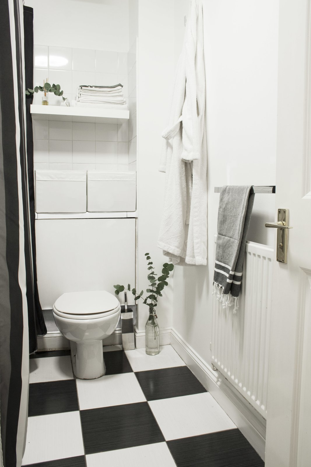Bath Room, Porcelain Tile Floor, One Piece Toilet, and Ceramic Tile Wall Though their wish was to redo the whole bathroom, they decided to stick to a budget and preserve the original black-and-white tiles, which are common in London flats. They ended up keeping it simple and accentuating the color palette with a black-and-white shower curtain and some new white storage elements.  Photo 8 of 8 in Two Architects Revive Their London Flat With Minimal Furnishings and a Fresh Dose of White