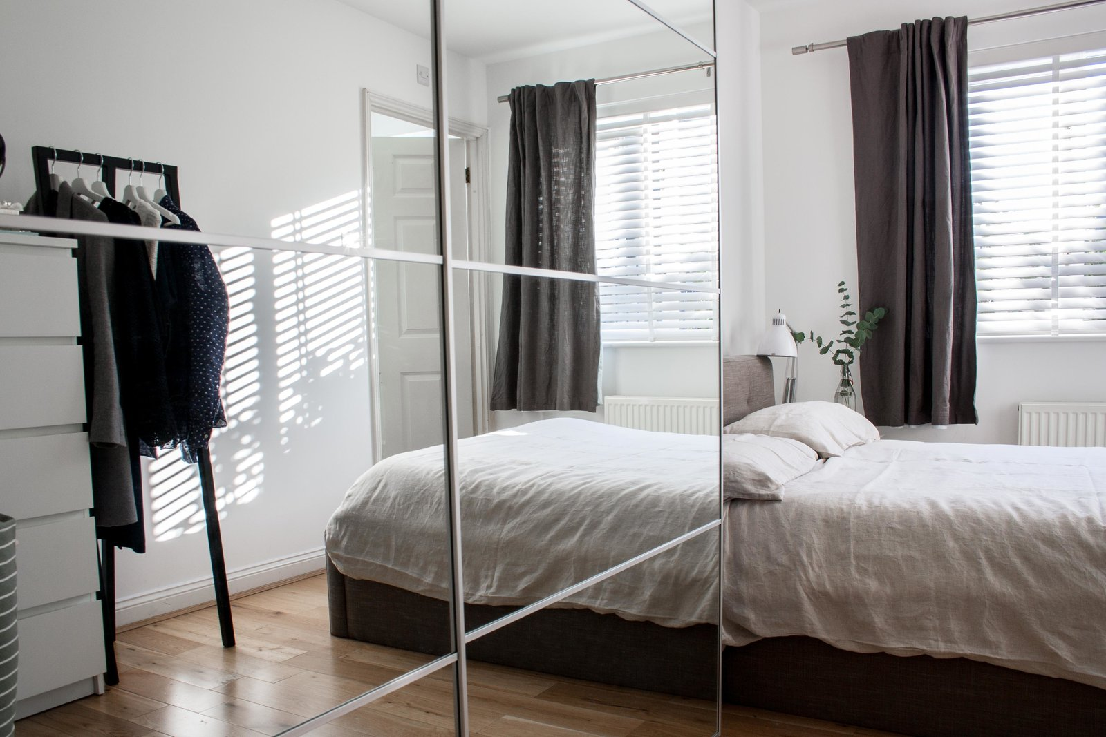 Bedroom, Bed, Night Stands, Lamps, Table Lighting, Light Hardwood Floor, and Wardrobe To create more storage and make the small bedroom feel larger, they purchased an Ikea wardrobe with mirrored doors. The clothing rack across from the bed is from HAY.  Photo 6 of 8 in Two Architects Revive Their London Flat With Minimal Furnishings and a Fresh Dose of White