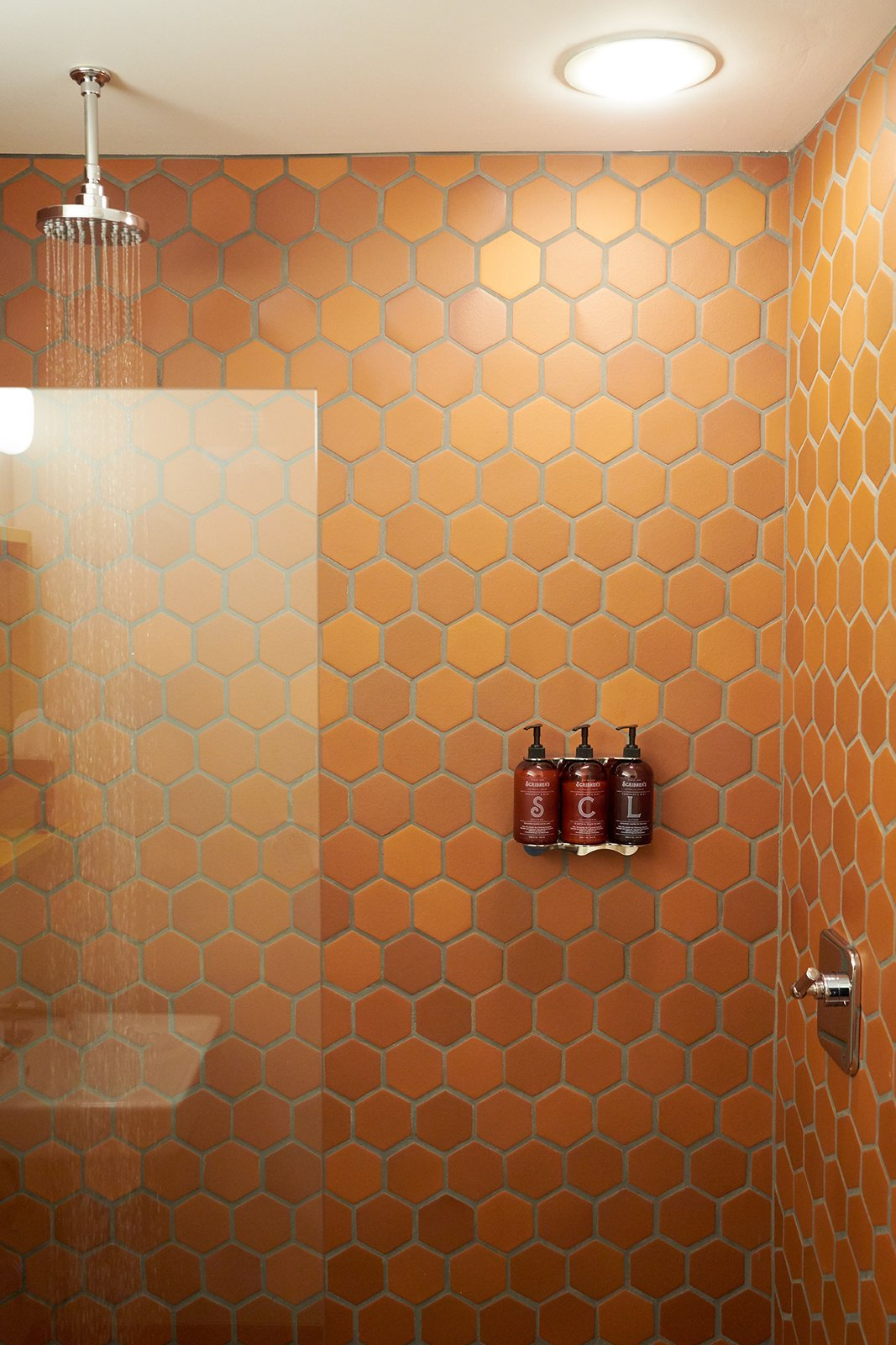 Each room's bathroom is equipped with showers lined with terracotta shower tiles, modern rain showers, and skin and haircare products made exclusively for Scribner's. Tagged: Bath Room, Enclosed Shower, and Ceramic Tile Wall.  Photo 6 of 14 in A Modern Mountain Lodge That Will Make You Love Winter Like Never Before