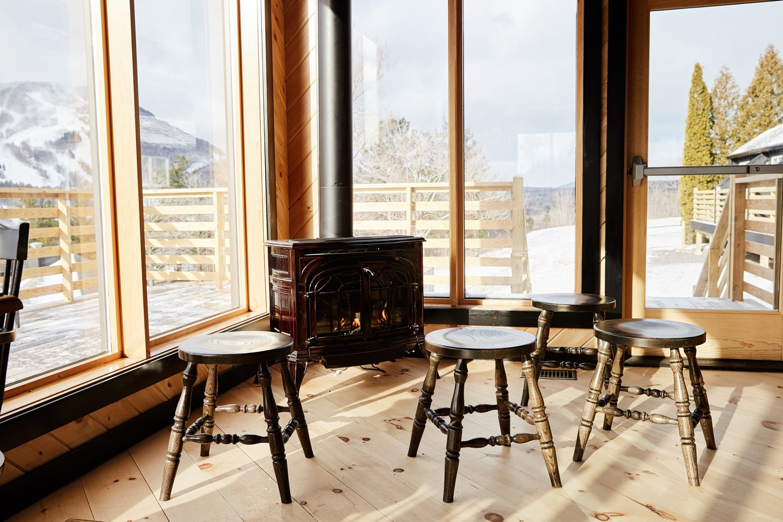 Living Room, Stools, Light Hardwood Floor, and Wood Burning Fireplace The restaurant looks out to 270-degree views of the Catskill Mountains and takes in ample natural light.  Photo 11 of 14 in A Modern Mountain Lodge That Will Make You Love Winter Like Never Before