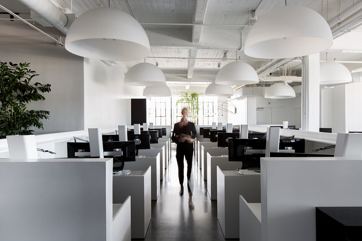 The central open work area is filled with white standing desks made by Muller Nichols and large Fontana Arte Dome pendants.  Photo 5 of 13 in A San Francisco Design Collective Reveals its Impeccably Cool Creative Studio