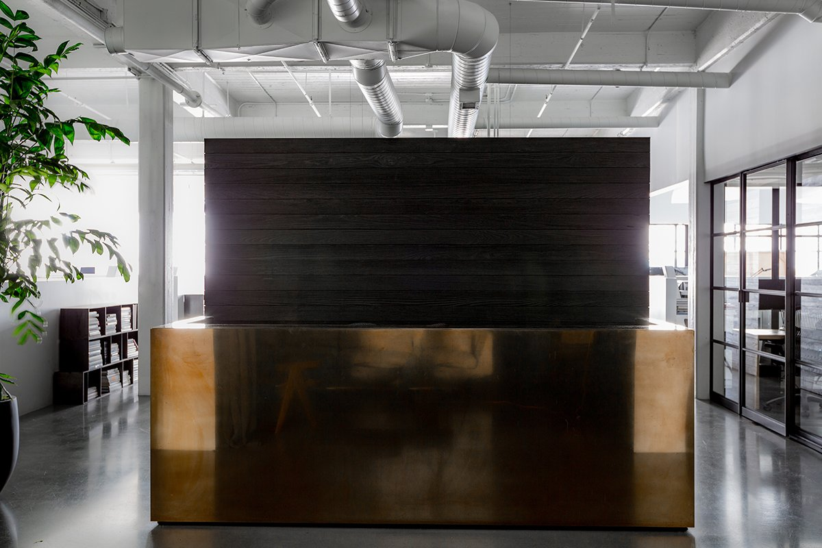 "Hollis points out, ""You move from a dark reception salon into a bright white open space. The contrast of moving from darkness into light is always part of my work."" The reception desk is a brass-clad box custom made by Chris French Metals—Hollis' ode to Donald Judd.  Photo 3 of 13 in A San Francisco Design Collective Reveals its Impeccably Cool Creative Studio"
