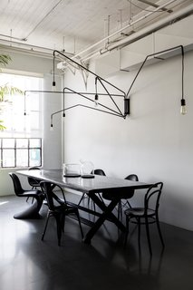 To create a place where employees and visitors can have family style lunches, they brought in a large dining table by James Perse. The hanging light is Lampada 046 by Dimore Studio.