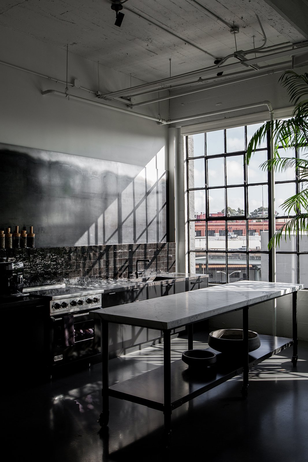 Directly next to the dining area is the dark kitchen, which has a custom island made with a metal base and a CoorItalia Calacatta marble top. Designed by Chris French, it's meant to invite socializing.  Photo 9 of 13 in A San Francisco Design Collective Reveals its Impeccably Cool Creative Studio