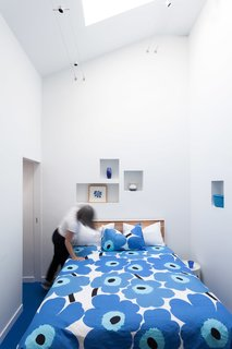Bright Colors and Sleek White Oak Fill This Playful Lake Tahoe Loft - Photo 4 of 9 - The cut-outs were added into the bedroom walls while the bed is outfitted with one of Marimekko's classic duvet covers.