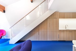 Bright Colors and Sleek White Oak Fill This Playful Lake Tahoe Loft - Photo 3 of 9 - The custom cabinetry is made with bleached rift-cut white oak and is finished with mirror pulls. Created by David Amble Cabinetry, the cabinets were designed to be put to serious use—one holds extra folding dining chairs while another hides a Murphy bed.