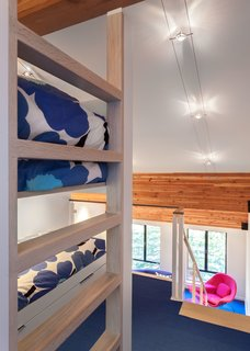 Bright Colors and Sleek White Oak Fill This Playful Lake Tahoe Loft - Photo 5 of 9 - When the family visits the vacation home, the kids sleep in custom bunk beds in the open loft.