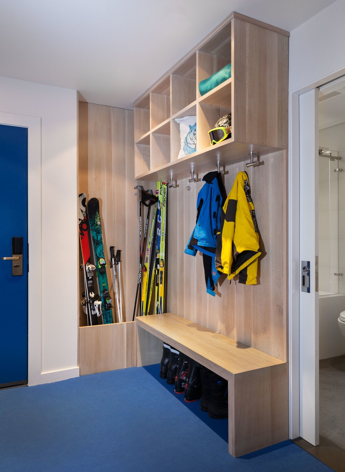 A cobalt blue door leads directly into a small entryway that's lined with custom cabinets for the family's skis, hats, boots, and jackets. Also created by David Amble Cabinetry, the trough is lined with copper so that the family can put their wet skis inside.  Photo 8 of 10 in Bright Colors and Sleek White Oak Fill This Playful Lake Tahoe Loft