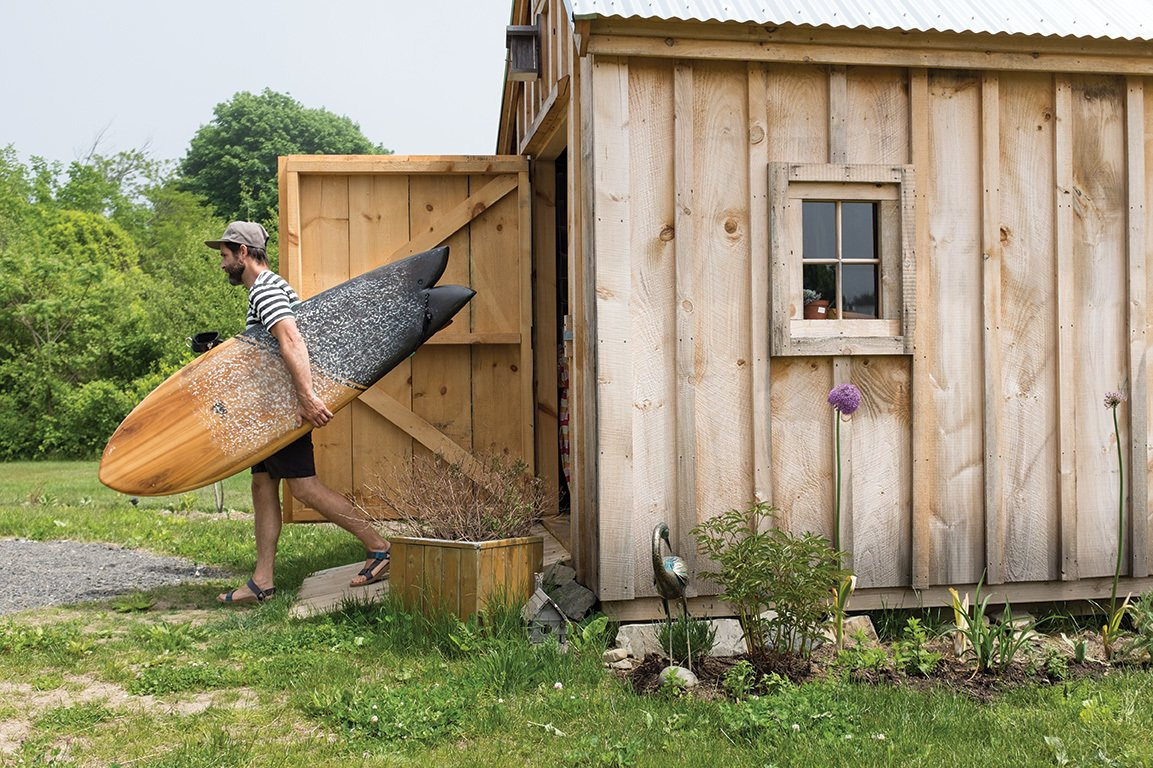 "As a photographer with an obsession with the sea, Nick LaVecchia recently finished building his new eco-friendly home in York, Maine. He spent two years researching the technical side and benefits of passive solar design. He's shown here carrying his 5'10"" fish board that he built himself. He learned directly from his brother Mike, who started Grain Surfboards in 2005.  Photo 9 of 11 in Indoek's New Book Shares a Glimpse Into the Homes of Creative Surfers"