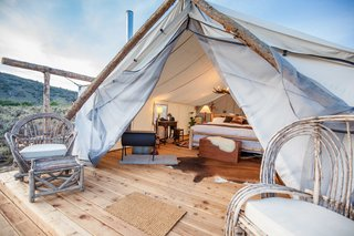 Each Signature Luxury Tent is built with wood floors and a canvas shelter. They're equipped with electricity, a working chandelier, high-quality bed linens, and a French press coffee bar. You'll also stay extra warm with a wood burning fire stove that's placed in every room, as well as a tea kettle that's at your disposal.