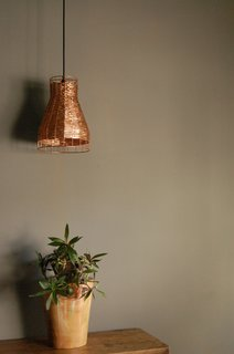 The process of turning recycled copper into a modern lamp can take one to two days per piece. Once the hammered or woven pieces are finished, they're heat-treated to seal in a patina, or polished for a copper shine.