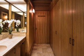 The only full privacy that exists in the main house—since everything is surrounded by glass—is in a cube that Jay placed in the center of the house. It's seven feet tall, covered with a thin sheet of fiberglass to let the light stream in from a skylight, and holds two-and-a-half bathrooms. The woodworking here is done with a mahogany finish.