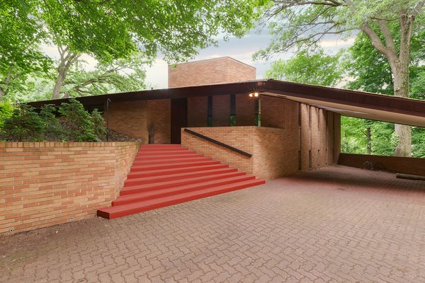 Though this home is close to downtown Minneapolis, it sits on a quiet, 3.77-acre piece of land. When you approach the brick home, it immediately becomes clear that it's a Frank Lloyd Wright-designed home—thanks to its wing-like shape and Cherokee Red-painted steps.  Photo 2 of 8 in The Original Homeowners of a Frank Lloyd Wright-Designed House Ask $1.3 Million