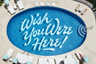 This Surf-Inspired Hotel Celebrates Waikiki's Creative Spirit and its Midcentury Roots - Photo 4 of 13 - Self-taught graphic artist Matthew Tapia hand-painted the illustrated text on the bottom of the pool.