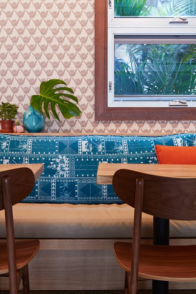 The aloha spirit runs deep in Mahina & Sun's, where the walls are covered with a shaka wallpaper by Andrew Mau. The cushions on the banquette seats were made with archived prints by Tori Richard, which were also used to create the headboards in the guest rooms and the men's uniforms.