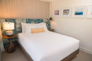 This Surf-Inspired Hotel Celebrates Waikiki's Creative Spirit and its Midcentury Roots - Photo 11 of 13 - The bedrooms are graced with headboards that Studio Collective created with vintage Tori Richard prints. The dreamy framed surf photography on the wall is by She Hit Pause Studios.