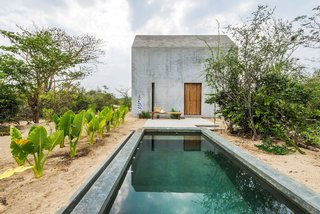"Named ""Casa Tiny"" for its small size, this minimalist concrete vacation rental designed by Aranza de Ariño is located on the Oaxaca Coast in Mexico near Casa Wabi, an artists' retreat founded by Mexican artist Bosco Sodi. With thick concrete walls on two of the facades, the end gables reveal a more porous relationship between inside and out, featuring windows and doors that open to the outside."