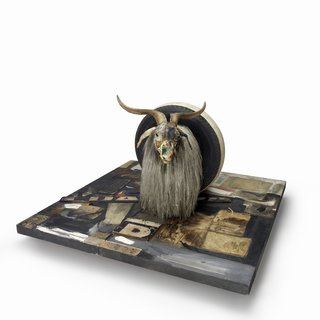 Monogram 1955-59 – Combine: oil, paper, fabric, printed reproductions, metal, wood, rubber shoe-heel, and tennis ball on two conjoined canvases with oil on taxidermied Angora goat with brass plaque and rubber tire on wood platform mounted on four casters.