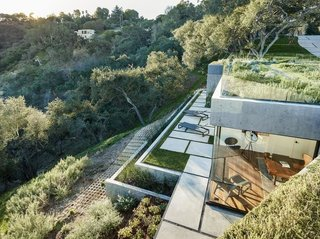 Constructed predominantly with structural concrete, the house can safely accommodate long, column-free spans and larger cantilevers, allowing it to visually integrate with the land.