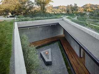 A courtyard on the lower level brings sunlight into the subterranean corridor where the bedrooms are located.