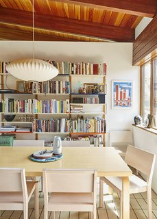 Michael Marriott bookshelves in an England home kitchen are paired with a Nelson bubble lamp and Artek table and chairs.