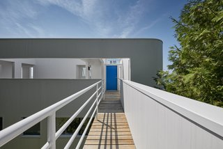 """The main entry, accessed via a footbridge that extends beyond the building envelope and into the site, leads to the upper-level floor. """"It is truly a house of opposites,"""" said the architect. """"To leave the house, for instance, you go up instead of down."""""""