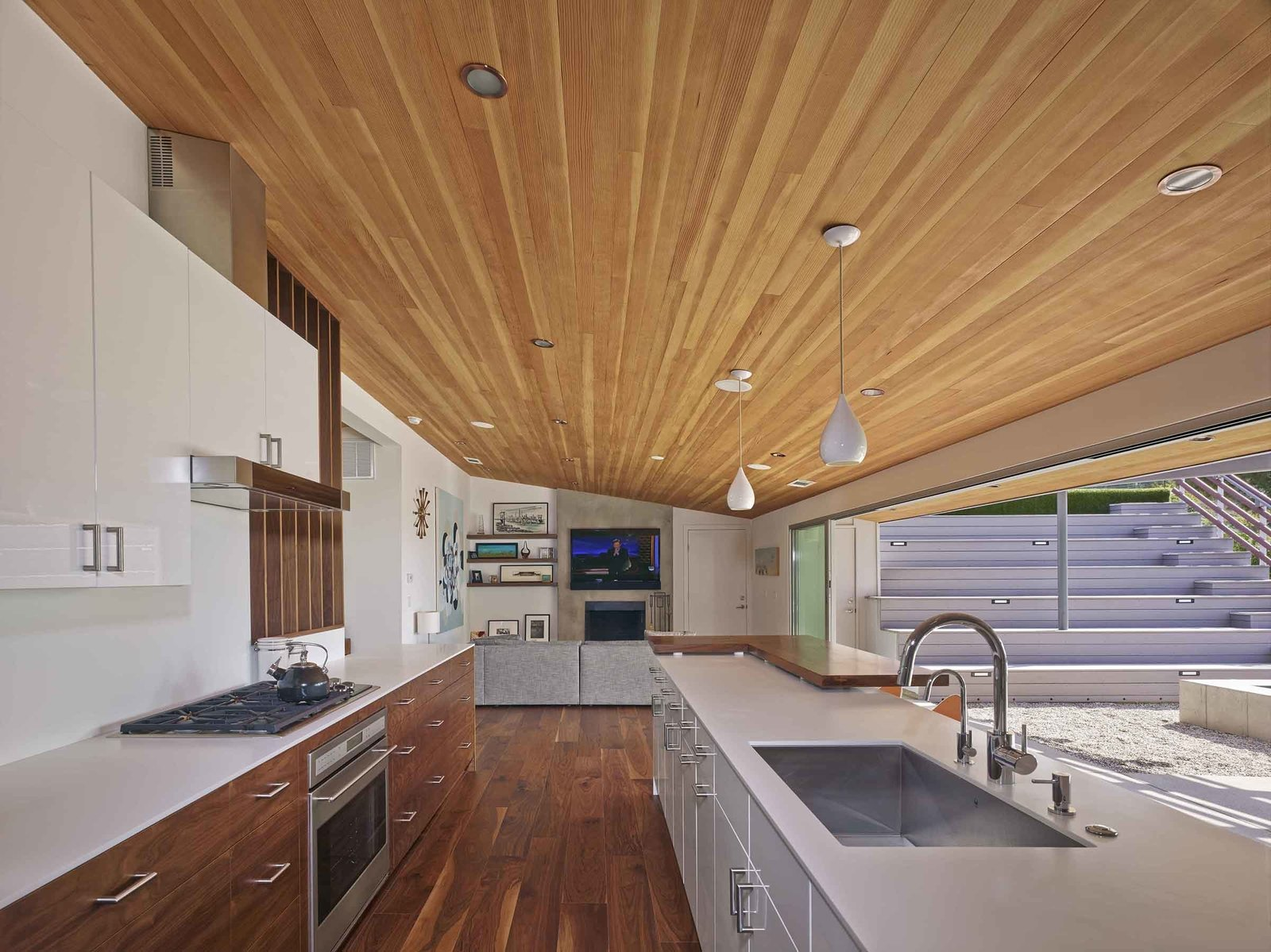"Kitchen, Wood Cabinet, and Medium Hardwood Floor ""By removing a few interior walls, reconfiguring a couple of others and opening up the kitchen/living/dining areas, we were left with a wonderfully livable floor plan with a great balance of public and private space,"" says Southerland. A large, open galley style kitchen and mirrored planes of wall paneling visually expand the home's interior perspective.  Photo 4 of 6 in A Mid-Century Modern Makeover in Los Angeles"