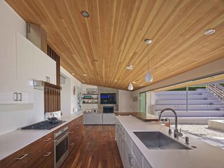 """By removing a few interior walls, reconfiguring a couple of others and opening up the kitchen/living/dining areas, we were left with a wonderfully livable floor plan with a great balance of public and private space,"" says Southerland. A large, open galley style kitchen and mirrored planes of wall paneling visually expand the home's interior perspective."
