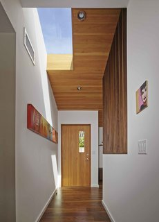 Striated wood paneling and new skylights give light and dimension to the renovated entryway.
