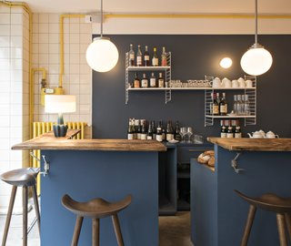 A set of wall-mounted String shelves, an iconic 1949 design by Nisse Strinning, provides storage for the casual bar, which features stools from By Lassen and wooden countertops.